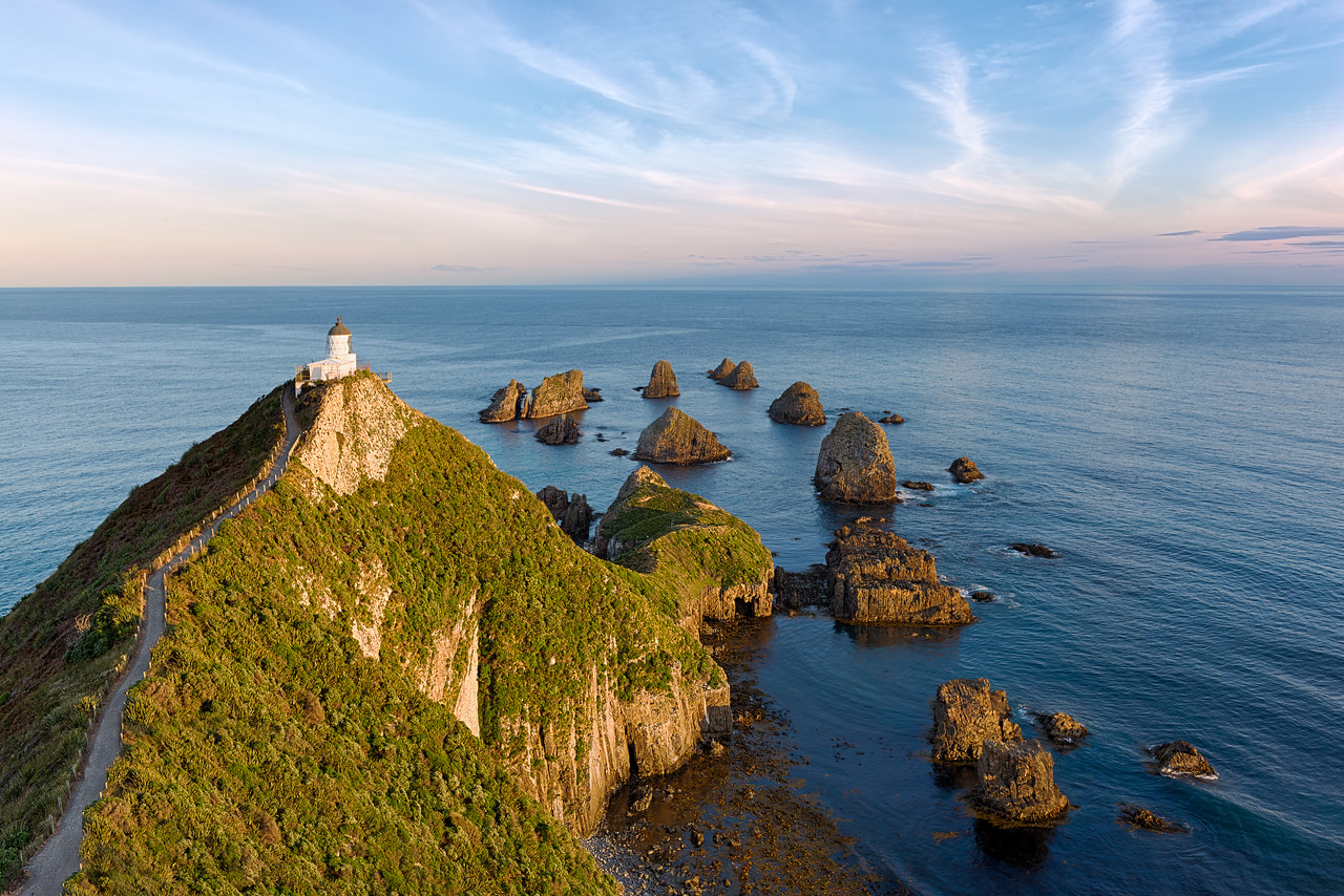 Warm light illuminates the beautiful Nugget Point Lighthouse in Southern New Zealand