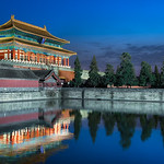 The south gate of the Forbidden City casts a soft reflection in the muddy waters below.