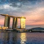 The Singapore Marina Bay Sands Hotel glows with golden light during sunset.